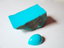 Photo of a piece of rough Turquoise with no matrix and nice blue Turquoise cabochon cut from that material.