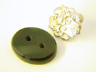 Photo of a cushion shape green stone with 2 holes of different sizes.