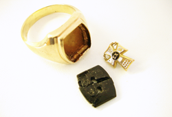 Picture of a man's ring with a barrel shaped Onyx with 2 holes and an emblem.