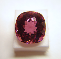 Photo of a cushion shape pink Tourmaline which has a window and needs to be re-faceted.