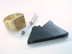 Photo of a square ring, a Diamond in a gold tube, a masonic emblem, and a piece of rough black Jade.