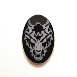 Photo showing the finished white image of a wolf onto an oval Onyx stone.