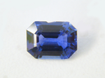 Photo of an emerald cut blue Sapphire with a chip in the side.