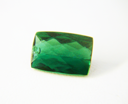 Shows a green Tourmaline cushion cut with a chip in the crown.