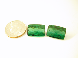 Shows a matched set of green Tourmaline cushion cuts.