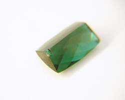 Photo of the same green Tourmaline with a chip in the pavilion.